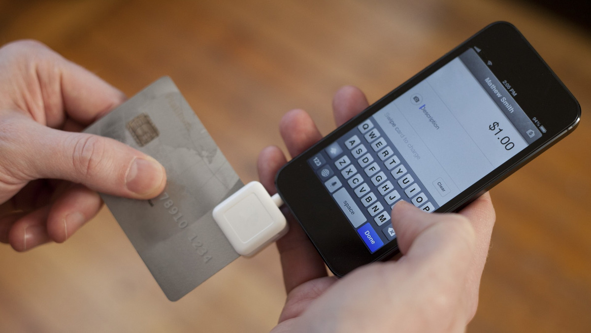 Close up of hands swiping card using mobile payment method on cell phone.