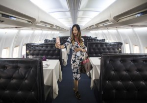 A woman takes a selfie inside china's first airplane restaurant
